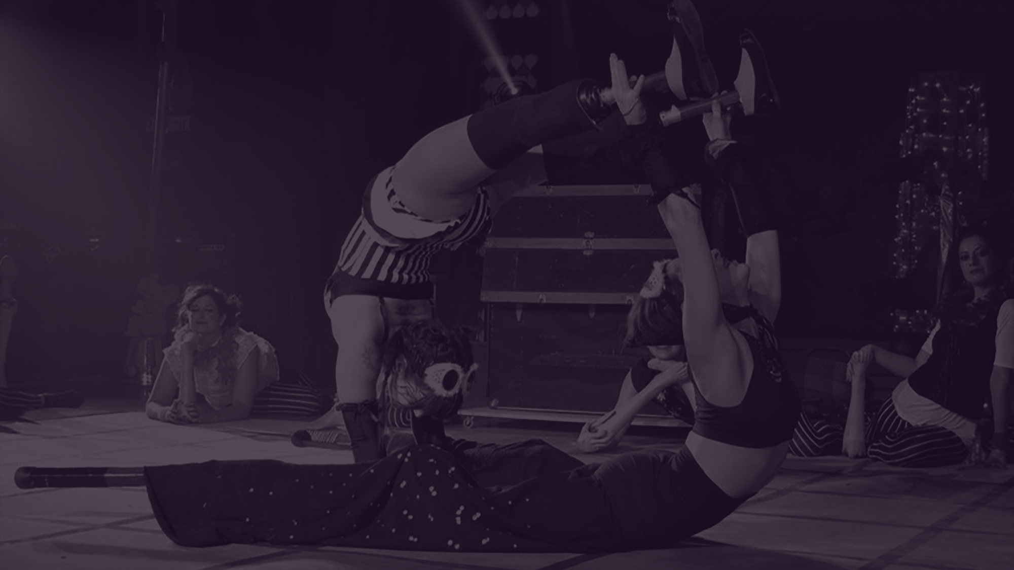 Black and white photo of Erin and Vanessa doing an acrobatic balance together that involves an arched handstand and an arch on the floor, with hands and prosthetic legs connected. The shape makes them look like a circle. There are people in the background making other shapes and holding plastic feet. Photo by Gilles Gelinas. Hospice Quinte Gala 2017. Lighting by Definitive Entertainment Productions.