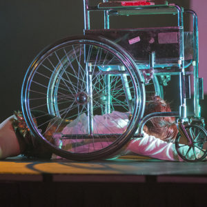 Erin is lying on her belly, one arm reaching forward, under a medical-looking, silver wheelchair.
